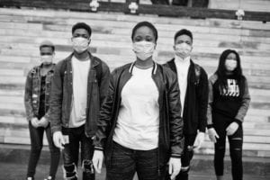 Group of masked young people standing and looking serious